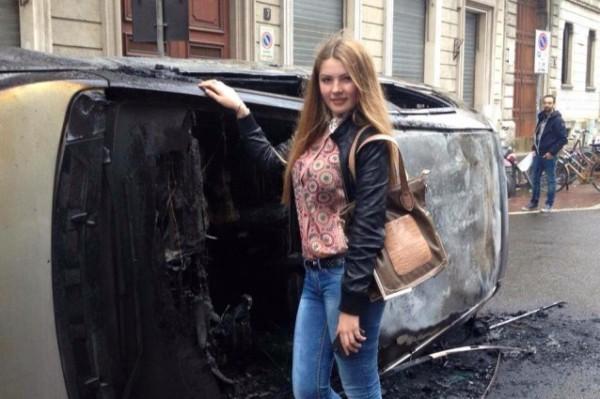 Una ragazza si fa una foto ricordo davanti a un'auto bruciata agli sconri del 1° maggo a Milano